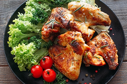 Ailes de poulet grillées aux légumes frais. Viande de poulet au four avec laitue et tomates cerises. Viande maison sur table en bois.